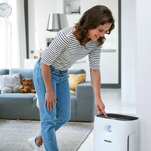Photo of Woman Turning on an Air Purifier